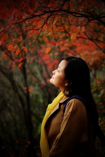 Thoughtful woman standing by autumn tree