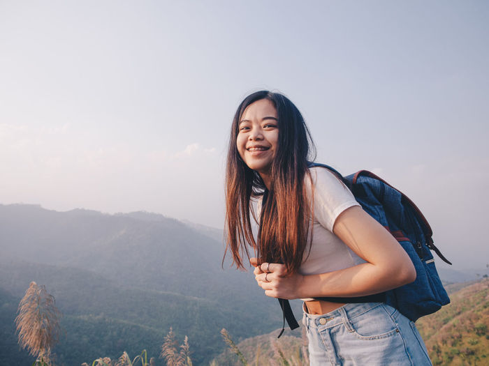 Wanderlust and travel concept from happy asian young woman walking trail in mountain
