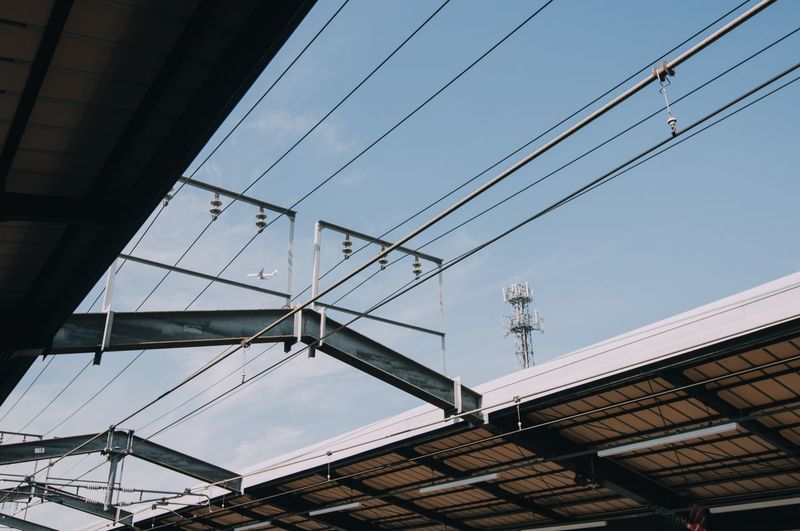 Low angle view of cables against sky at railroad station