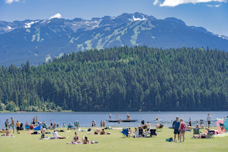 Hot Summertime Swimming Beach Blue Sky Clouds And Sky Crowd Dock Forest Group Of People Lake Large Group Of People Leisure Activity Lifestyles Mountain Mountain Range Mountain Town Mountains Outdoors Ski Resort  Ski Resort Summer Summer Swim Water