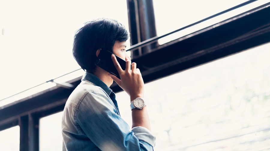 Side view of young man talking on phone against window