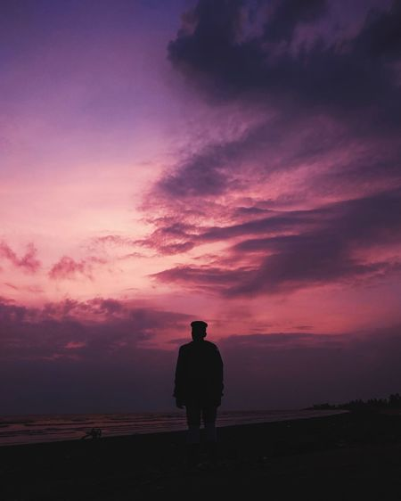 Rear view of silhouette man standing on land against sunset sky