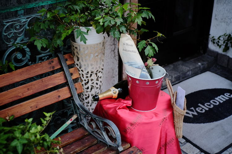 High Angle View Of Empty Champagne Bottle With Bucket On Stool By Bench