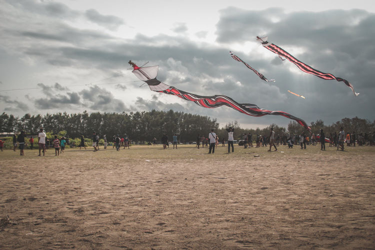 This is a Balinese Kite Balinese Cloud - Sky Cooperation Crowd Day Flying Group Of People Humaninterest Kite Kite - Toy Land Large Group Of People Leisure Activity Men Nature Outdoors Real People Sky Sport Streetphotography Team Sport Teamwork