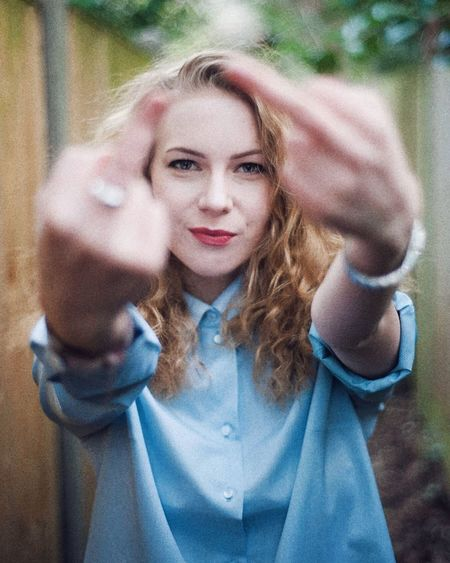 Portrait of young woman making obscene gesture