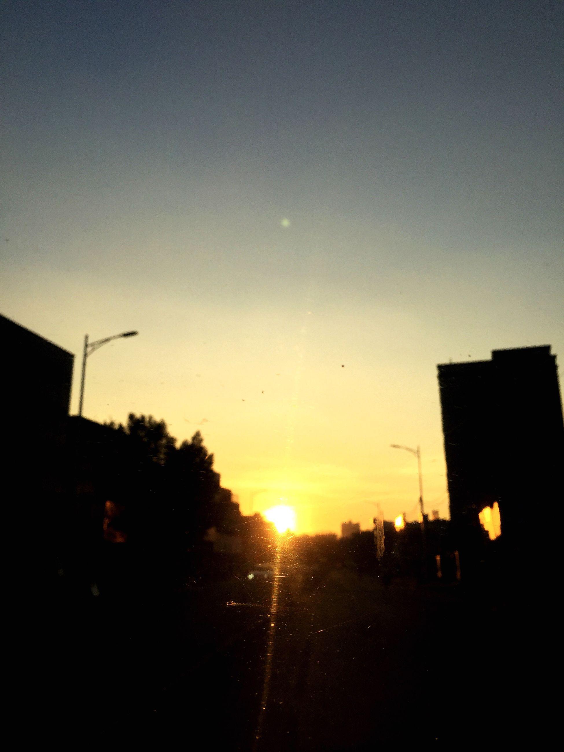 sunset, sun, silhouette, building exterior, built structure, architecture, clear sky, sunlight, copy space, orange color, sky, lens flare, tree, sunbeam, car, house, nature, outdoors, transportation, no people