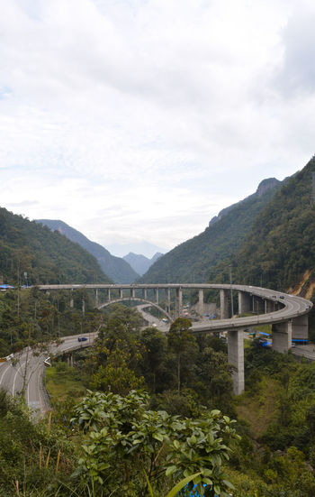Bridge over mountains against sky