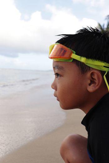 Portrait of boy wearing sunglasses on beach against sky