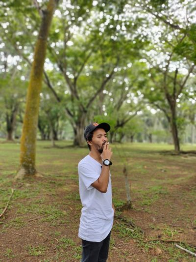Man smoking cigarette while standing at park