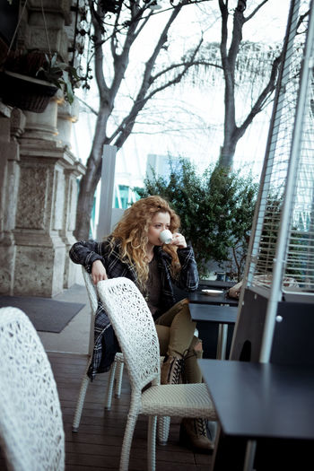 Young blonde woman taking a break at a coffee bar. Serious expression, looking away. Architecture Blonde Building Exterior Casual Clothing City Life Day Focus On Foreground Leisure Activity Lifestyles Long Hair Person Tree Wavy Hair Young Adult Young Women
