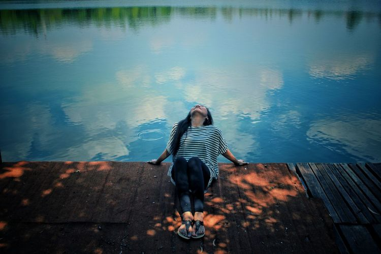 Woman standing by lake against sky