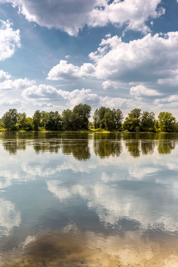 Lazy summer day at river bank. Line of trees at oposite bank makes symmetry Beauty In Nature Cloud - Sky Day Growth Idyllic Lake Nature No People Non-urban Scene Outdoors Plant Reflection Reflection Lake Scenics - Nature Sky Tranquil Scene Tranquility Tree Water Waterfront