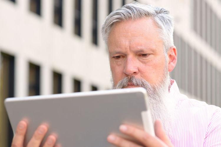 Man using digital tablet outdoors