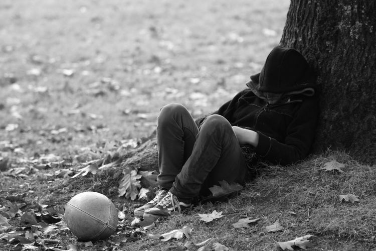 Boy napping by rugby ball in park