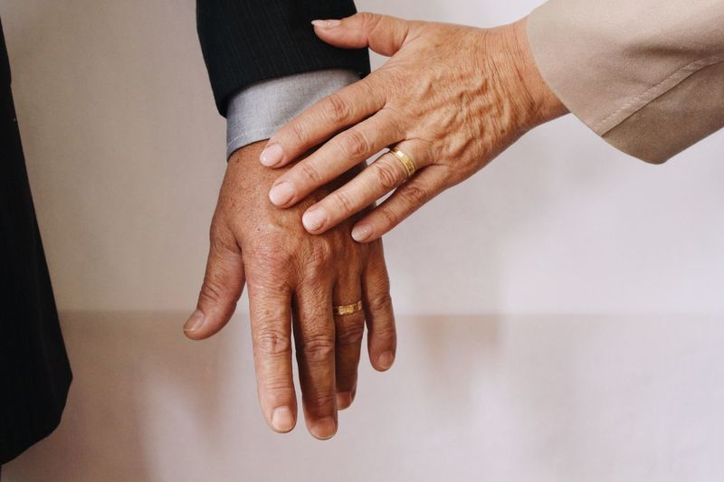 Midsection Of Mature Couple Holding Hands
