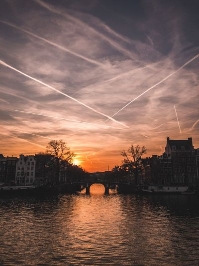 Sky Architecture Cloud - Sky Built Structure Sunset Water Nature Building Exterior Silhouette No People Orange Color Outdoors Building Dramatic Sky Cityscape Waterfront Scenics - Nature Beauty In Nature Vapor Trail