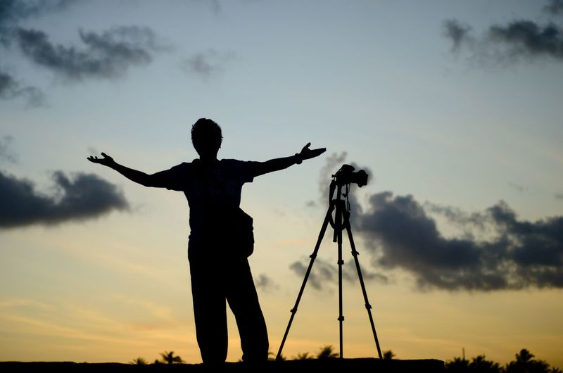 Scenic view of photographer silhoutte on the sunset background. Happy Man Man Alone Wallpaper Background Malaysia Beach Weapon Sunset Men Sport Silhouette Standing Full Length Tree Politics And Government Golf Club Tripod Dramatic Sky Camera Sky Only Cloudscape Lightning Storm Cloud