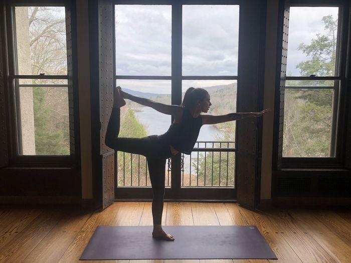 Full length of woman exercising against lake seen through window