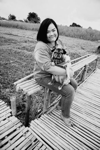 Portrait of woman with dog at agricultural field
