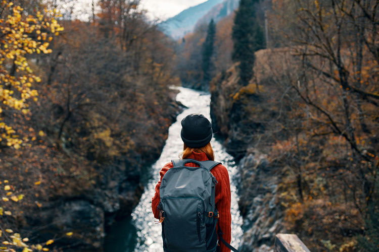 Rear view of person standing on rock during autumn