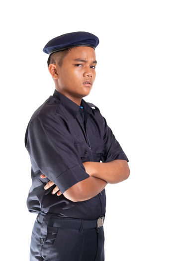 Young Asian man in police uniform isolated on white background. White Background Studio Shot Cut Out One Person Clothing Looking At Camera Standing Young Adult Cap Portrait Men Police Officer Security Face Smile Service Occupation Indoors  Uniform Three Quarter Length Young Men Hat Confidence