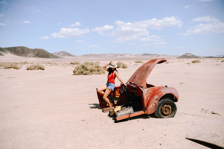 Full length of woman sitting on abandoned vehicle at desert