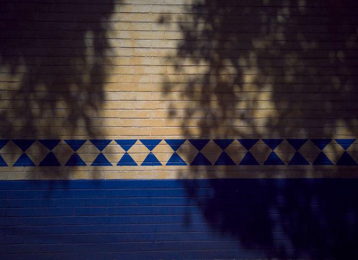 Shadow of wall on tiled floor