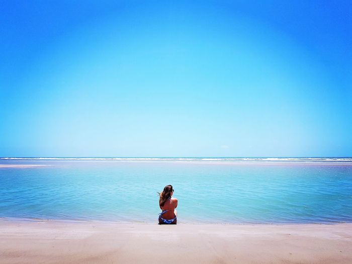 Rear view of woman looking at sea while sitting at beach against clear sky