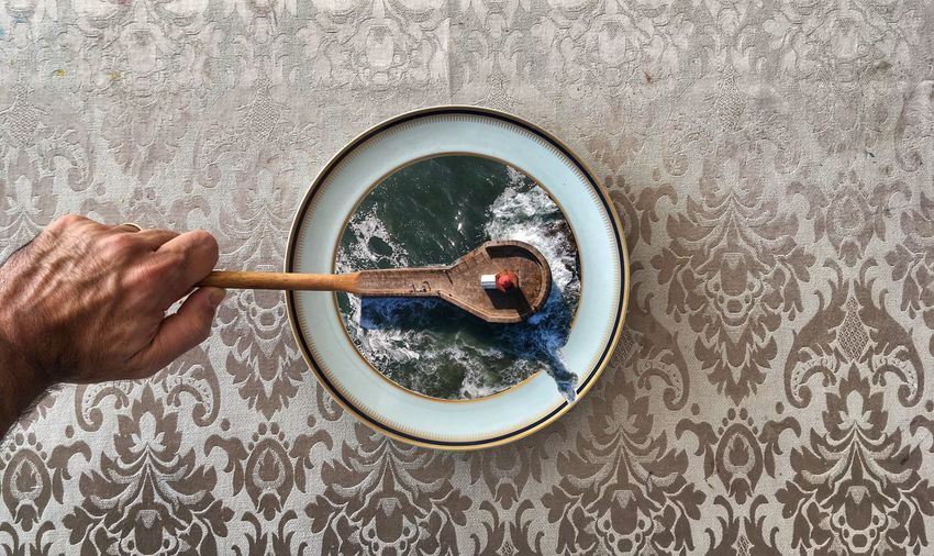 Directly above shot of cropped hand holding spoon over plate with waves art