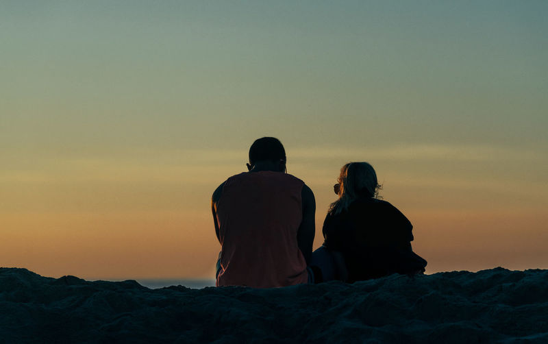 Couple sitting on beach overlooking the ocean sunset in Ocean Beach of San Diego, California Travel Vacations Valentine Valentine's Day  Beach Couple Commitment Domestic Partnership Sunset Couple Sunset Couple Togetherness Vacation