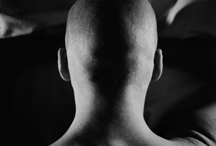 Young man from behind, shirtless, shaved head, ears and neck, listening to the world, meditation