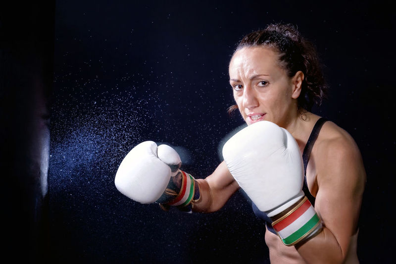 Portrait of woman practicing boxing against black background