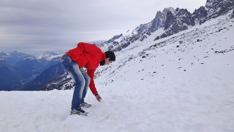 Man Picking Up Snow On Mountain