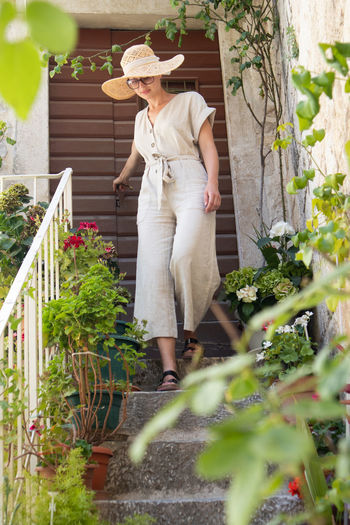 Midsection of woman standing by flower plants
