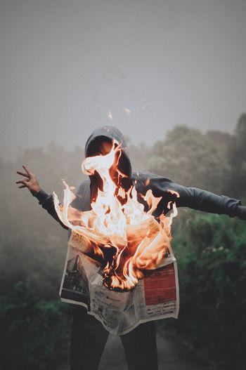 Man Standing By Burning Newspaper