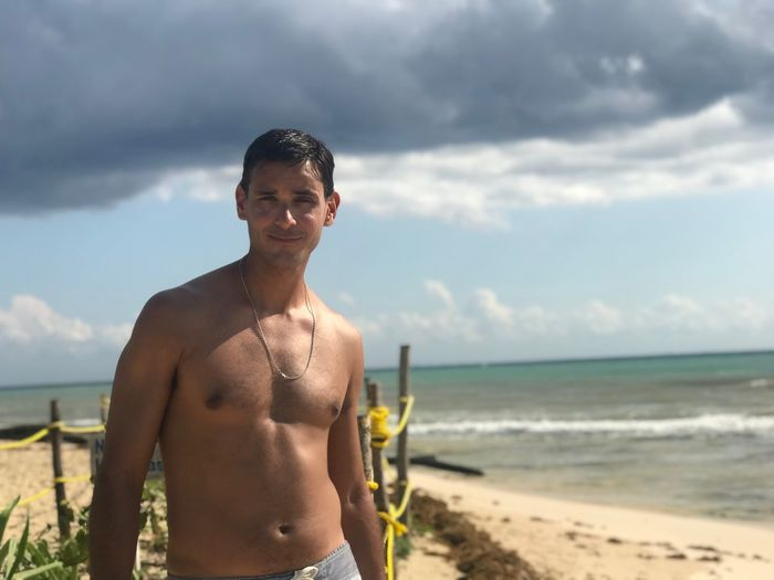 Portrait of shirtless mid adult man standing at beach against cloudy sky