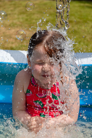 Close-Up Of Playful Girl Splashing Water In Wading Pool