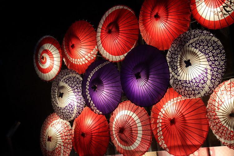 Illuminated umbrella hanging at market stall