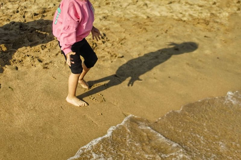 Beach Body Part Casual Clothing Child Day Full Length High Angle View Human Body Part Land Leisure Activity Low Section Nature Offspring One Person Outdoors Sand Shadow Shorts Sunlight Water