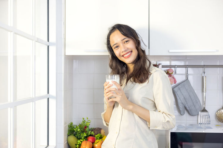 Portrait of smiling young woman standing against wall at home