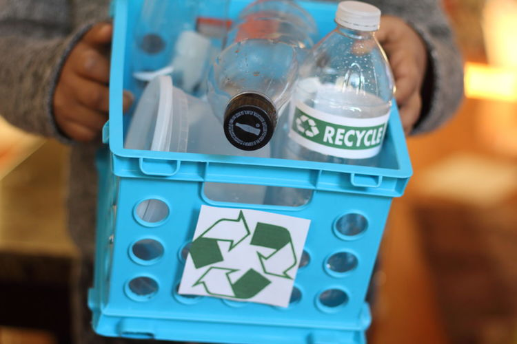 Midsection of person holding basket with plastic bottles