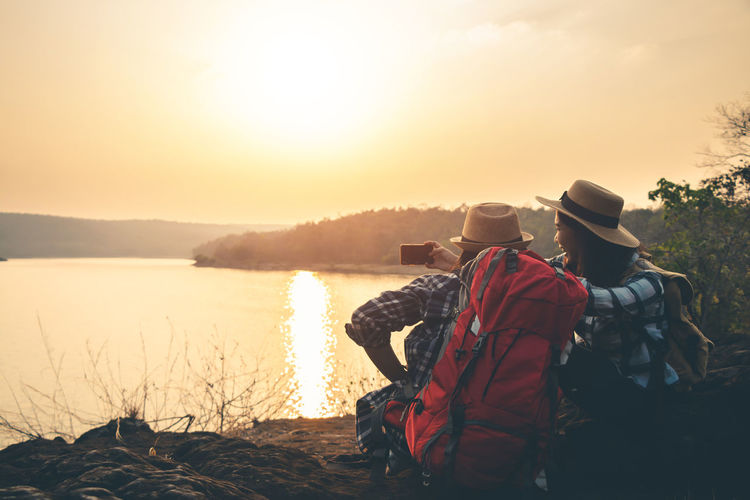 Lifestyles Nature People Outdoors Landscape Backpack Backpacking Backpacker Travel Map Women Sky Sunlight Two People Hat Water Real People Sunset Beauty In Nature Rear View Togetherness Scenics - Nature Adult