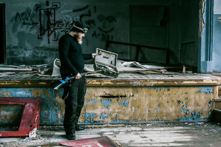 Full Length Of Man Standing With Gun In Abandoned Room