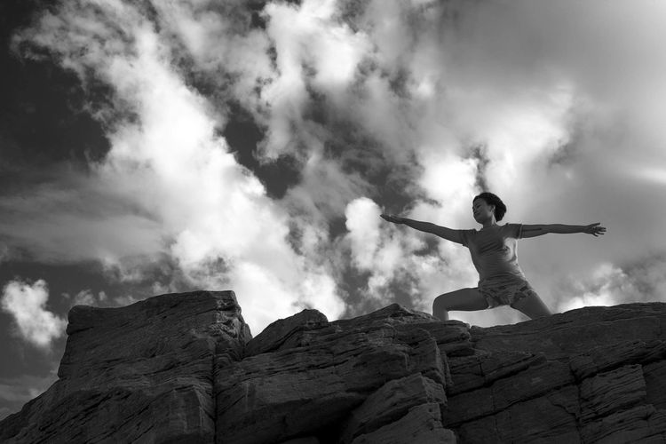 Low Angle View Of Woman Stretching With Arms Outstretched Against Cloudy Sky