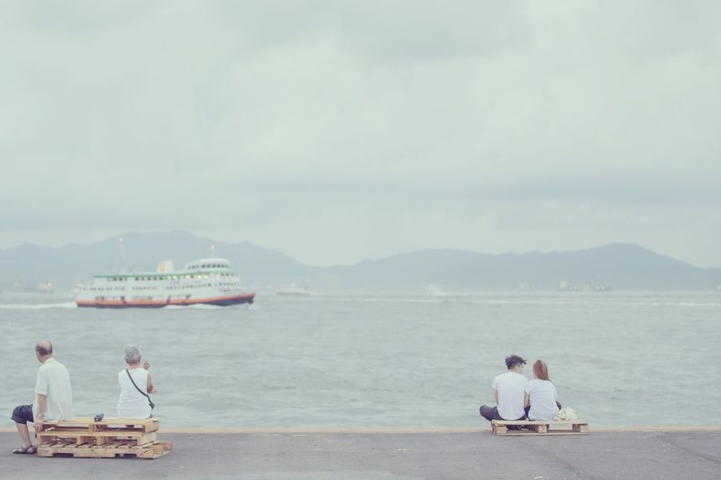 Young And Senior Couples Overlooking Boat Sailing On River