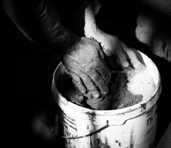Cropped image of man mixing sand and water in bucket