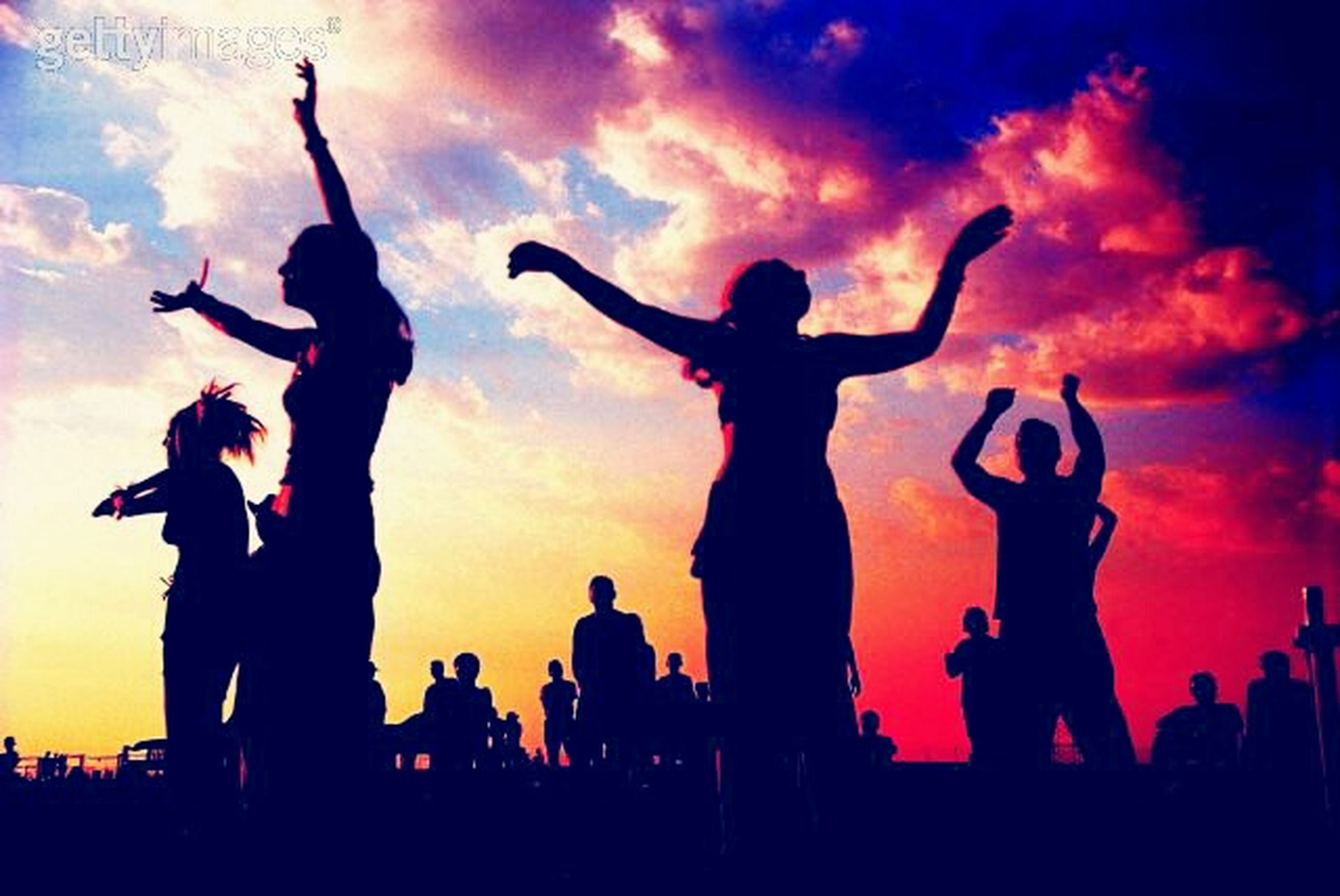 silhouette, sunset, large group of people, sky, enjoyment, leisure activity, men, lifestyles, togetherness, fun, orange color, arms raised, arts culture and entertainment, cloud - sky, person, performance, excitement, standing, crowd