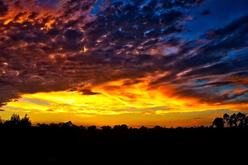 Silhouette landscape against dramatic sky during sunset