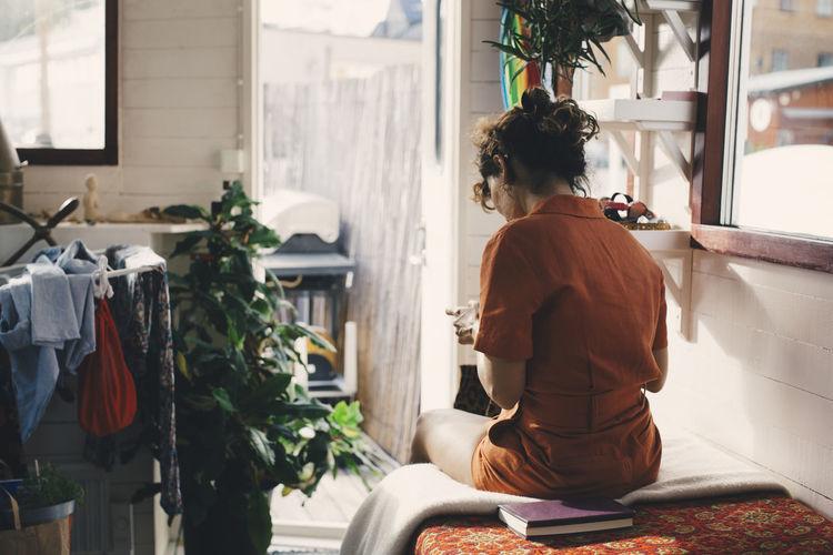 Rear view of woman sitting by window