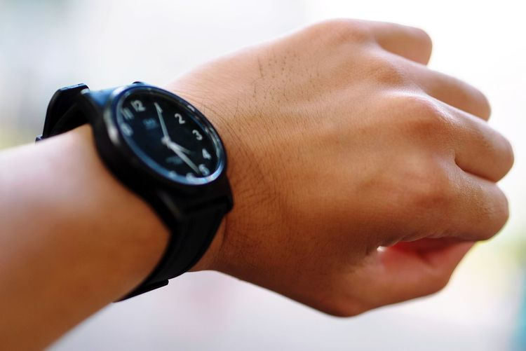 Close-up of human hand wearing wristwatch